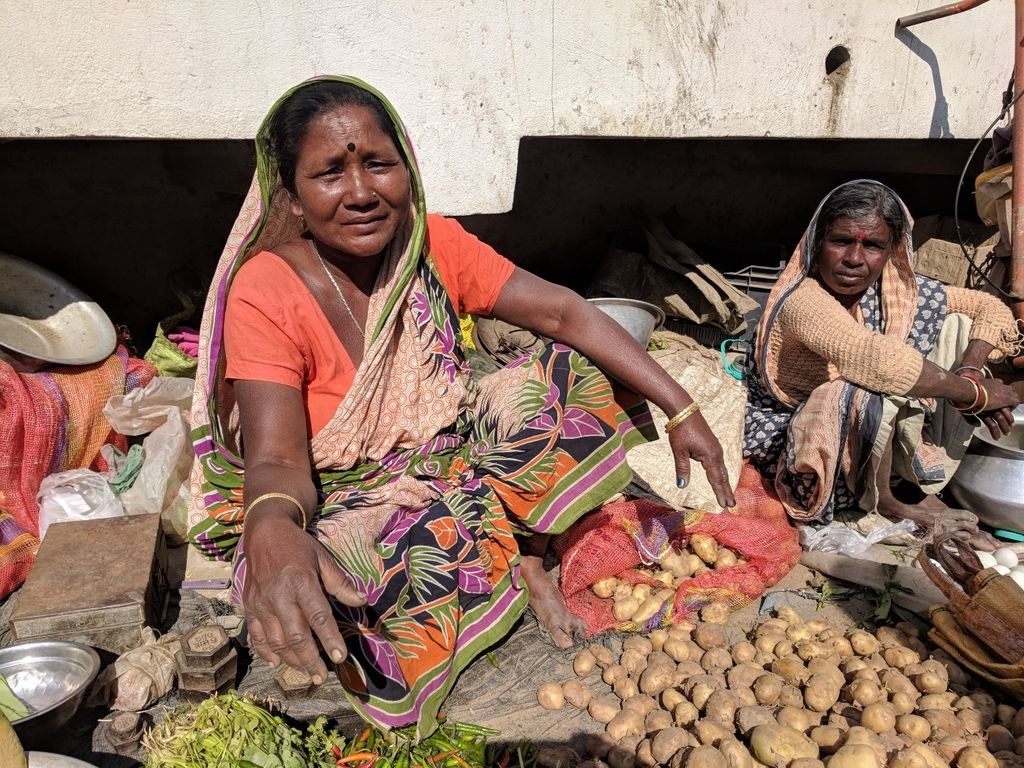 Two women look at the camera while surrounded by produce