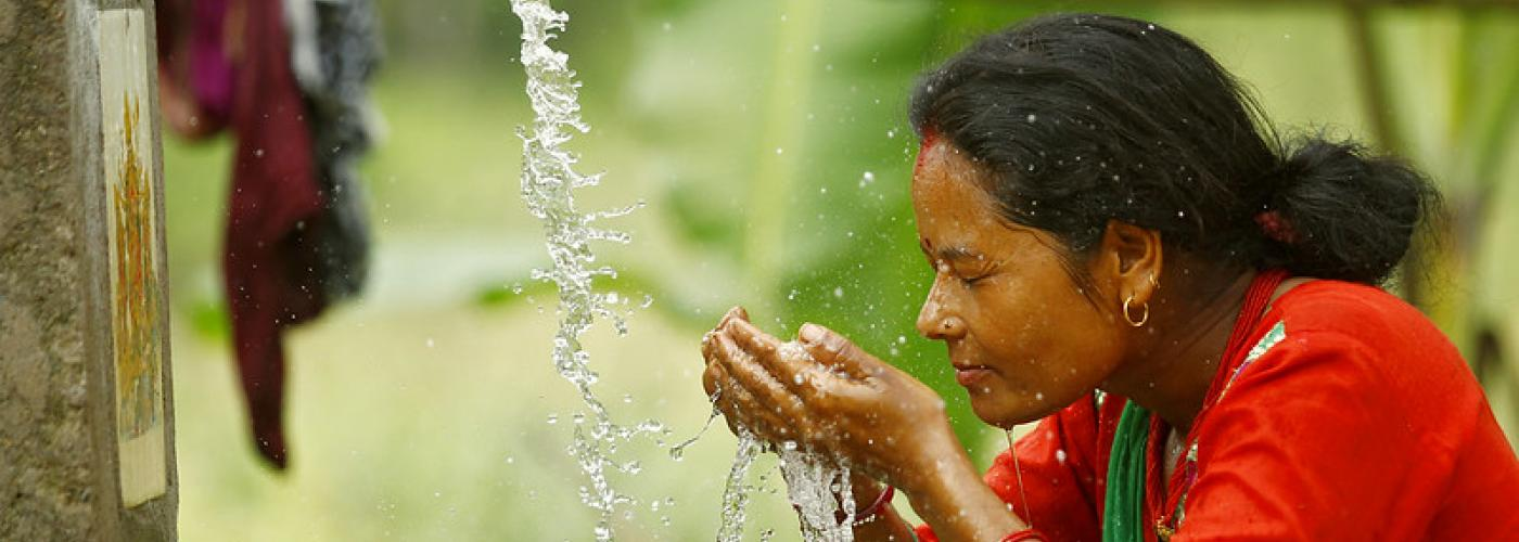 Photo: Chandra Kala Thapa, one of many smallholder women farmers from the Ranichuri village in the  Sindhuli district at a water faucet gathering water in her hands.