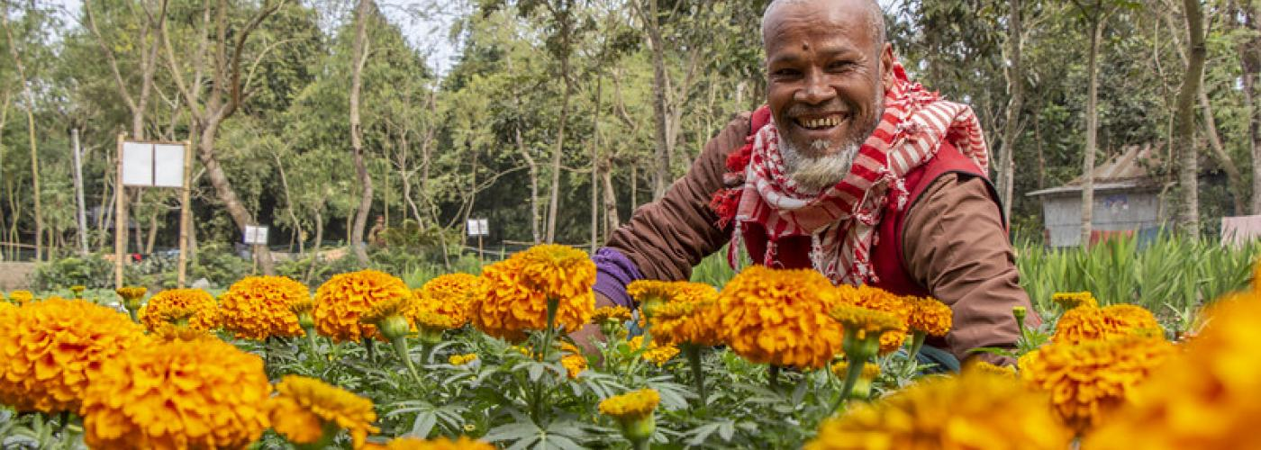 Photo: man standing in field of flowers facing camera and smiling