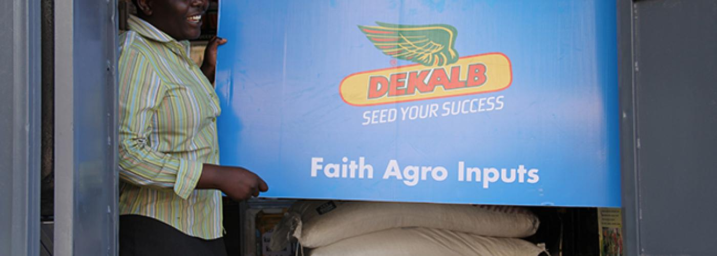 Photo: Woman holds up sign for Dekalb Seed for Success Agro Inputs above bags of grain.