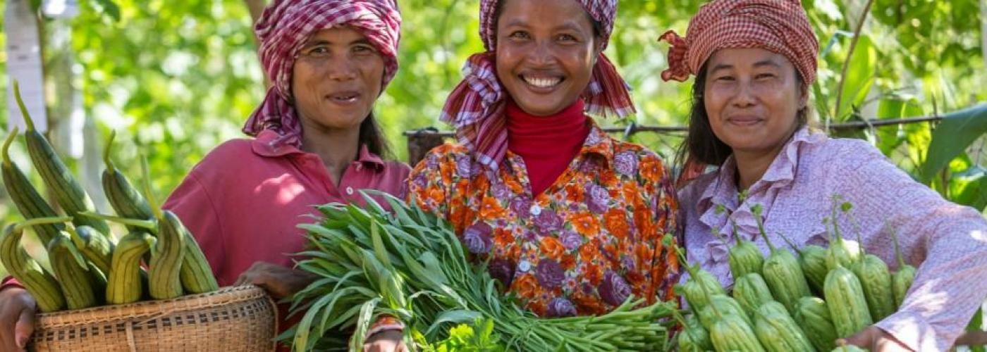 Three women smile at the camera while holding produce