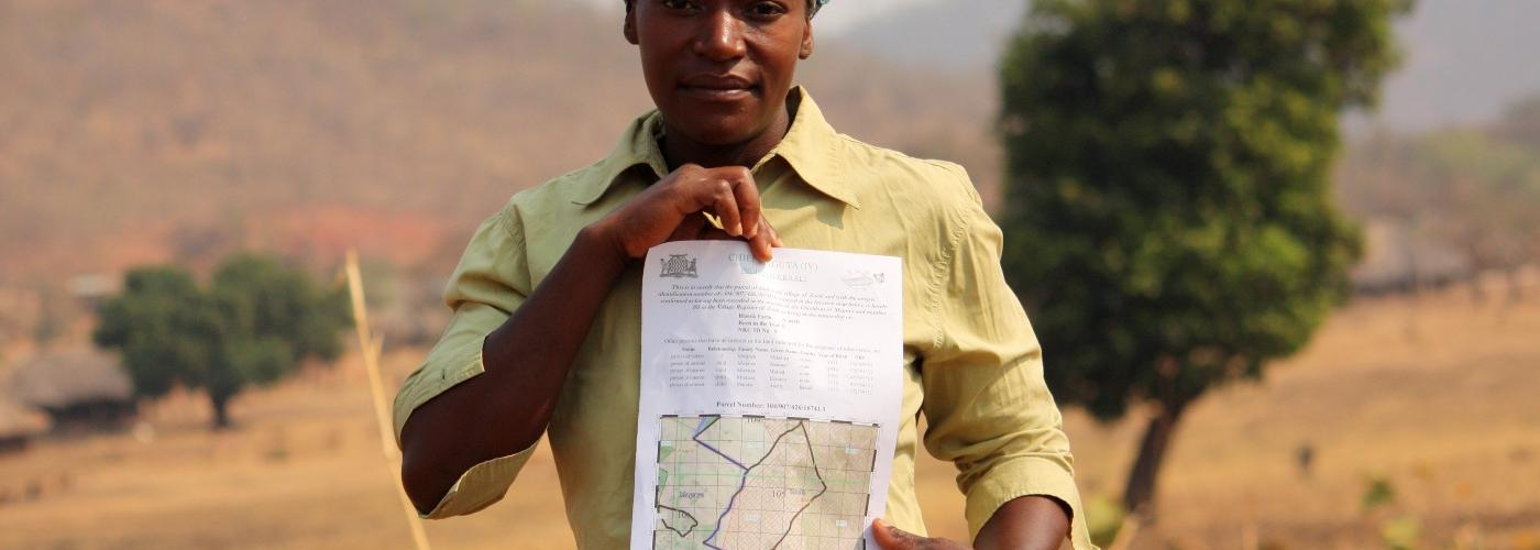 A woman looking at the camera, holding her customary land certificate on her parcel of land in eastern Zambia