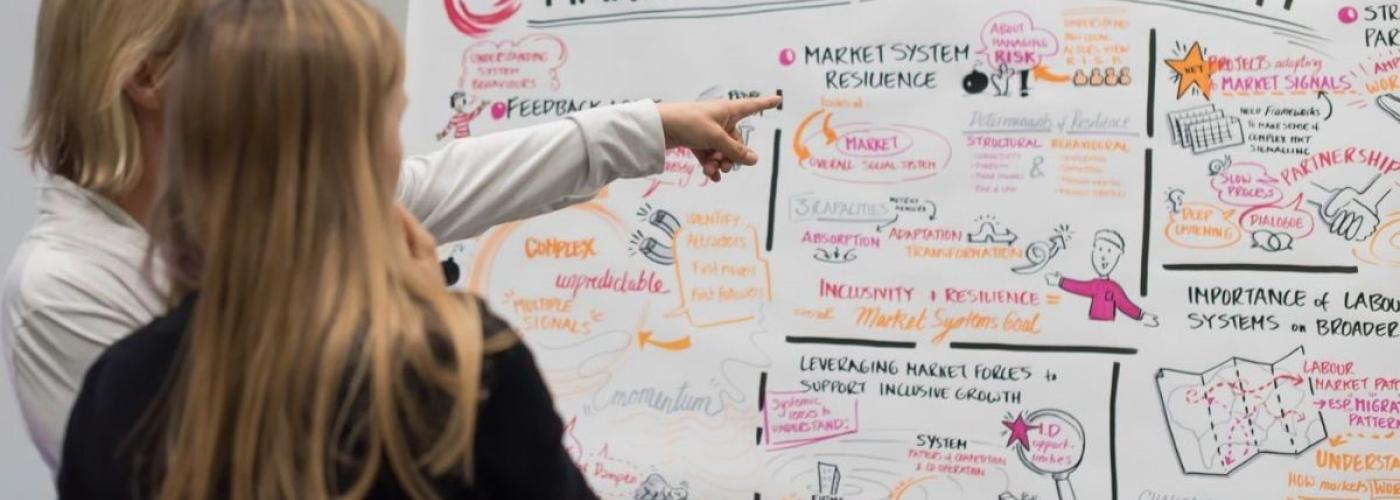 A woman points to a dry erase board with market system symposium information on it