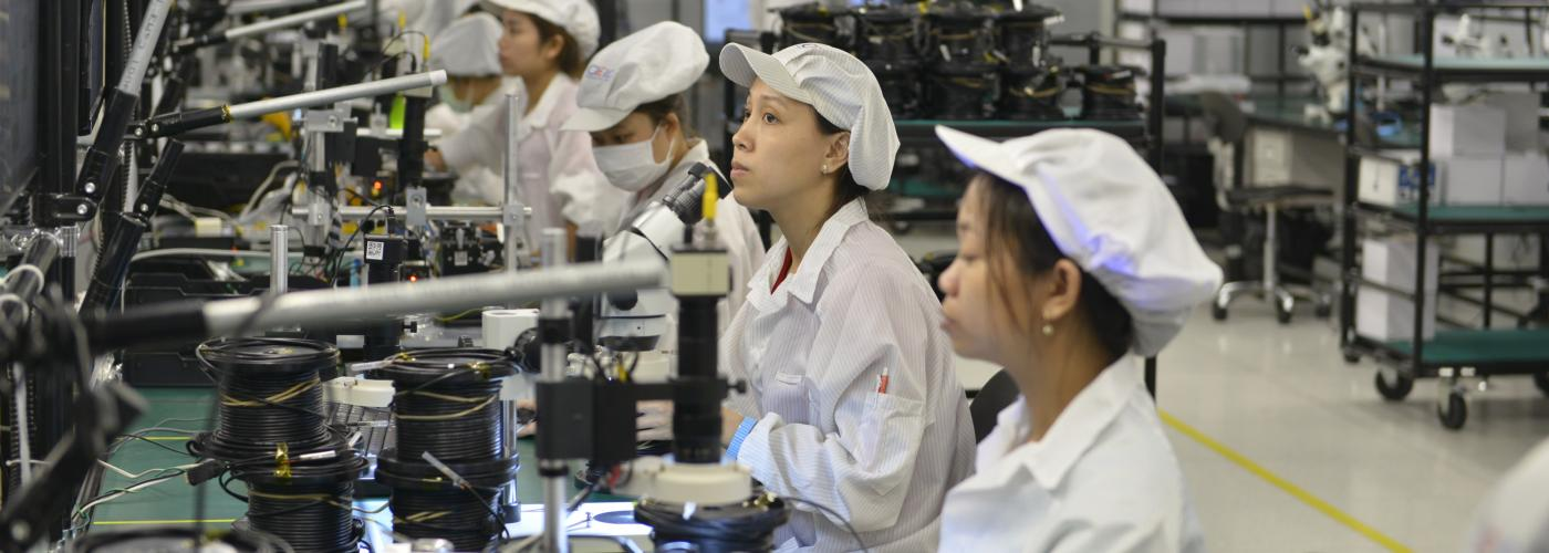 A row of factory workers wear white at a row of workstations.