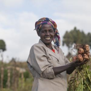 A woman smiles at the camera while holding potatoes