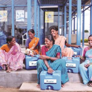 Five women in Inda smile at each other while holding WaterHealth vending machines