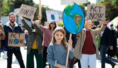 A young girl holds a handmade sign of the Earth at a climate protest