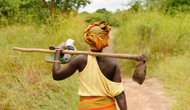 A picture of a female farmer with a hoe