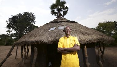 A Fenix customer in front of his solar-powered home. © Fenix International