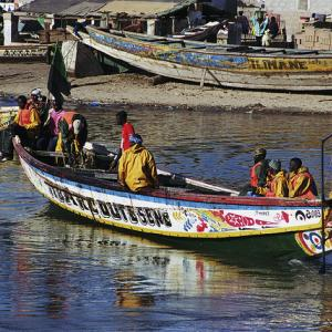 Municipal sanitation workers carry trash aboard boat. Photo: Scott Wallace / World Bank