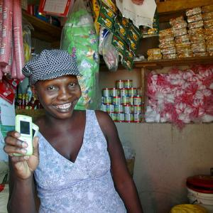 Participant in the Mobile Money (wallet) Program in Haiti holding a phone in a market.