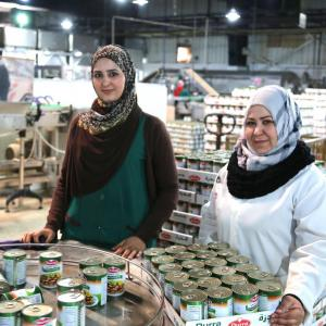 Photo: A Jordanian and Syrian woman working together in a Syrian-owned food processing factory forced to relocate to Jordan due to the conflict. The company employs some of its former Syrian workers who are now refugees in Jordan, as well as local Jordanian staff.