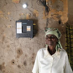 Photo: Woman standing next to an electricity generator, looking at camera.