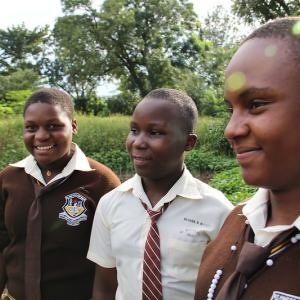 Photo: Shown standing in a demo garden at St. Paul's College, Nelima, Bridget, and Philomena are proud members of the Youth Farmers Club at their secondary school in Mbale, Uganda.