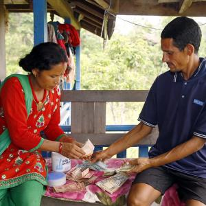 Photo: Chandra Kala Thapa along with her husband Bir Bahadur Thapa keep track of income from the sale of recently-harvested eggplant.