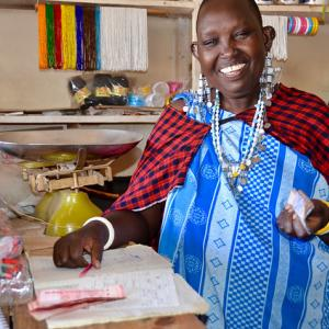 Photo: Woman in Tanzania working in her shop in the local market of Mamura village. Photo Credit: UN Women/Deepika Nath