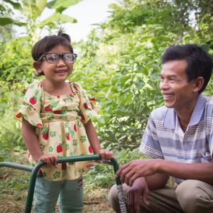 Photo: three-year-old Sreyna with glasses and a walking frame to help her see and learn to walk, standing with adult male, her father