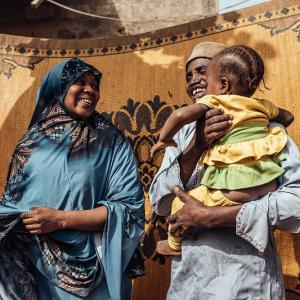 Photo: Nigerian woman and man standing in front of a cloth. The man pictured is holding a baby.