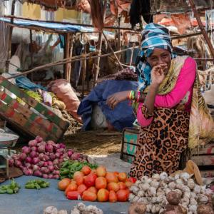 A women kneels in her vegetable market. Photo Credit: Mejia, CIMMYT