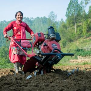 Photo: Asha Thapa Magar uses her newly purchased mini-tiller on her farm. Photo Credit: Robic Upadhyaya/KISAN II, Winrock International