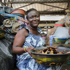 Photo description: A woman sells fish at a market in Togo.