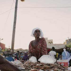 A women stand in front of a fish market. Photo Credit: Melissa Cooperman, IFPRI, November 2019