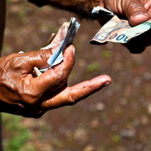 Hands holding cash near Munduk waterfalls in Bali. Photo by Bindalfrodo, Flckr.