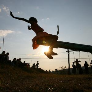 In Swaziland, just before sunset, a young girl tests out a new seesaw on a playground.