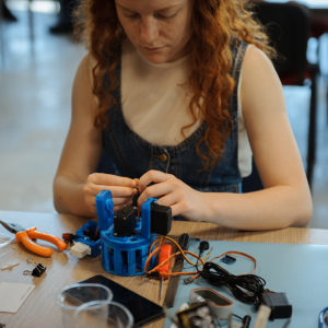 Photo: woman using tools and working on a technology project.