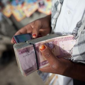 Photo: hand holding stack of money and mobile phone