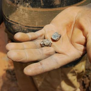 Photo description: A miner holds a piece of cassiterite in his palm in the DRC. Credit: Laura Heaton/Enough Project.