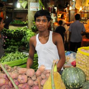 Photo: A young man sells his produce in a Dhaka market in Bangladesh.