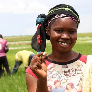 Young girl smiling at camera while standing on a farm holding up a seed