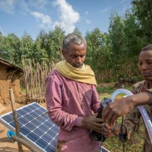 Sewagegn, a local smallholder farmer, and Gebeyaw, a data collector, set up Sewagegn's solar powered pump to irrigate her backyard garden in Danghesta, Amhara region of Ethiopia