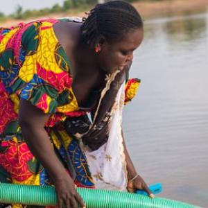 Women pump water from a river in Senegal