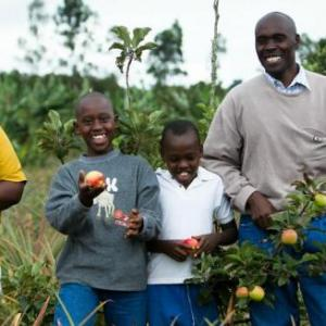 A family happily displays their fruit tree crop.