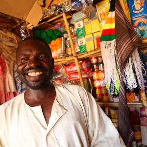 A man stands in his shop, smiling at the camera