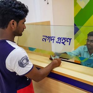 A man completes a transaction with a banking agent in rural Bangladesh.
