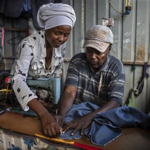 A man and woman work with a sewing machine