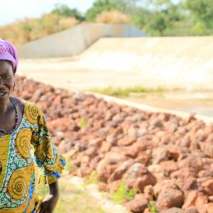 Photo: This member of a rice growers cooperative stands in front of a dam constructed by USAID for lowland rice farming.