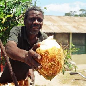 Photo: Man holding a coconut, facing the camera