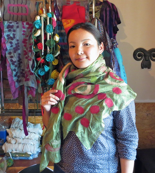 Nurjamal stands with her textiles.